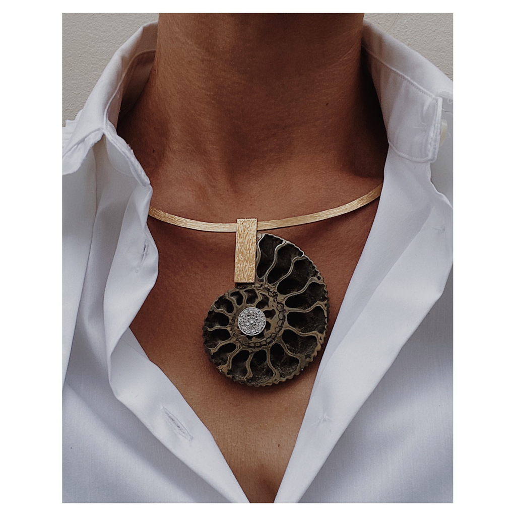 A fossilised ammonite set in yellow gold, highlighted by diamonds on a yellow gold collar, by Francesca Grima.