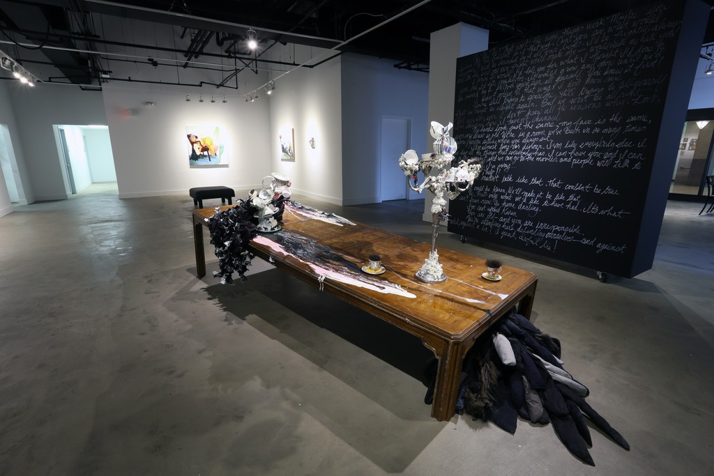 The black wall features text from the performance piece by David Antonio Cruz, greenhowiwantyou, green.  Installation of a brokenn table with paint, paper with resin, sculpture and costumes pieces from past performances.