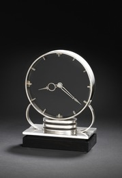 A rare art deco sterling silver table clock. Black lacquered clock face with sterling silver numerals and hands. Rectangular ebony base.