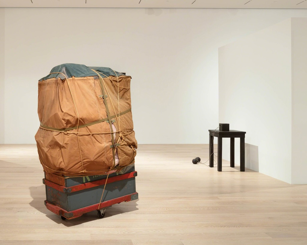 "Christo, Dolly, 1964 Wooden box, tarpaulin, polyethylene, rope, girth, and metal wheels. Courtesy the artist. Joseph Beuys, Tisch mit Aggregat (Table with Accumulator), 1958–85. Bronze, wire cables. Courtesy Galerie Thaddaeus Ropac, London, Paris, and Salzburg. Installation view: ""The Everywhere Studio,"" Institute of Contemporary Art, Miami, Dec 1, 2017–Feb 26, 2018. Photo: Fredrik Nilsen Studio."