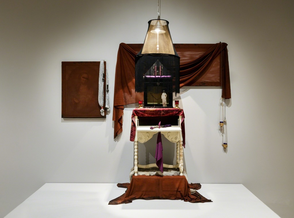 "Robert Mapplethorpe. ""Untitled (Altarpiece),"" 1970. Fur, silk scarf, table hammer, tablecloth, fabrics, candles, candleholders, glass box, wood boxes, frame screen, cast-iron claws with glass ball, lamp bulb, lampshade, holy water in glass bottle, Jesus figurine, framed chromolithograph, crates. Private collection and Robert Miller Gallery, New York © Robert Mapplethorpe Foundation"