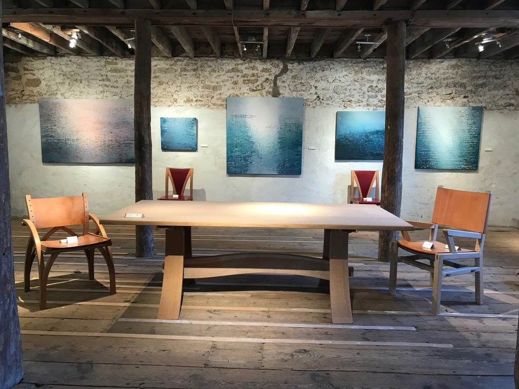 Luke Elwes' Ganga paintings with furniture by Petter Southall. Right to Left: The Scandia leather chair, the solid oak Refectory Table, Two Red leather Soft Chairs and the Treble Zero Lowback chair in steam-bent oak and oak-bark-tanned leather.