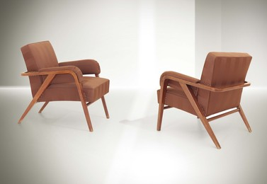 a pair of armchairs with a wooden structure and fabric upholstery