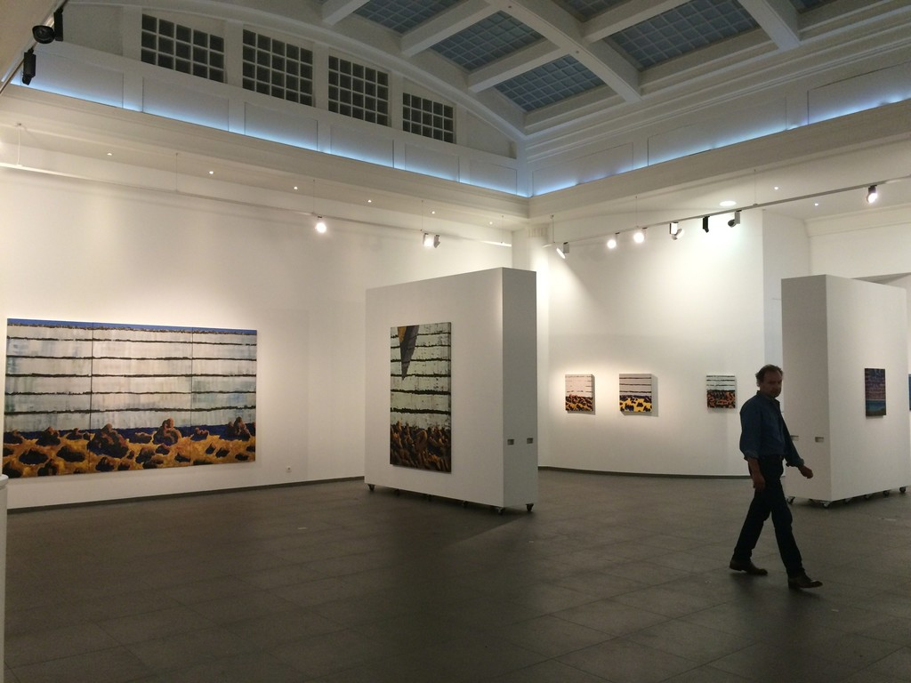 "The artist in the exhibition space, with ""Falaise, Chaos de plage, Tryptique"" (135 x 325 cm, Oil on Canvas, 2016)"