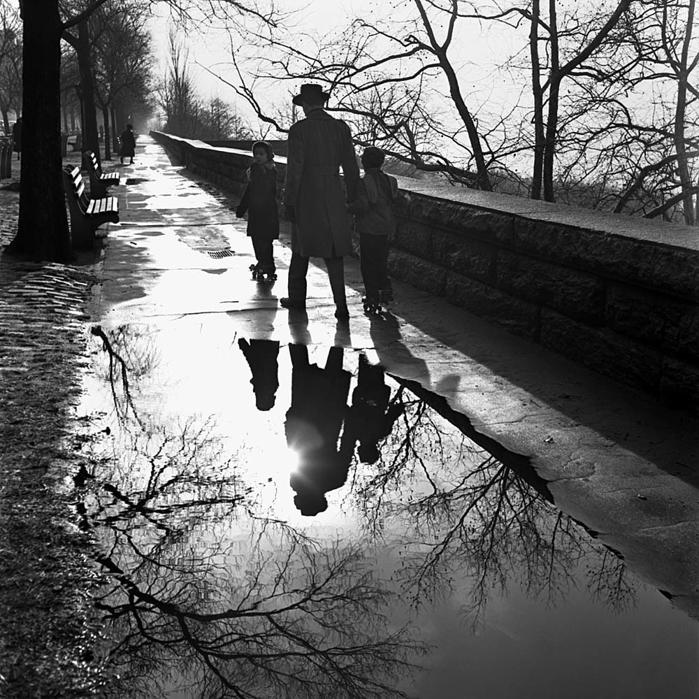 1241, Father and children rollerskating on sidewalk