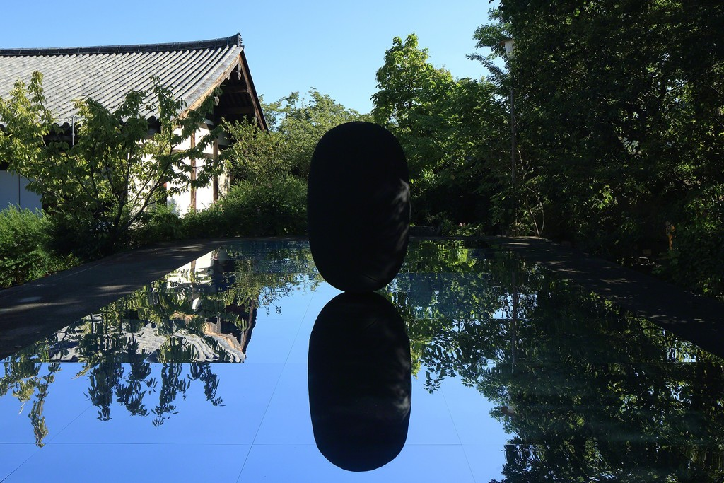 Kimsooja, Deductive Object, 2016, black casted aluminum on mirror, 1.83m x 1.1m (sculpture), 8m x 5m (mirror). Gangoji Temple, Nara, Japan. Commissioned by Culture City of East Asia 2016, Nara. Photo by Keizo Kioku. Courtesy of Art Front Gallery Co., Ltd. and Kimsooja Studio.