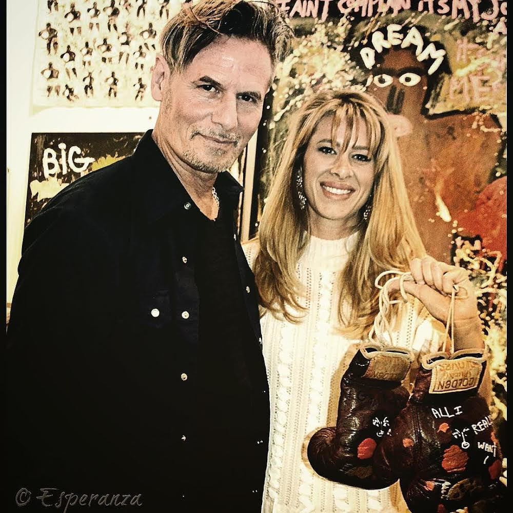 """Artist Richard Kurtz with new collector • Art Palm Springs 2018 Hi young woman was bullied as a child, so because a boxer. She collected these painted boxing gloves for her home gym. """"All I Really Want Is You""""  Casein on found vintage boxing gloves. • Esperanza Projects  One of our hashtags is #artheals"""