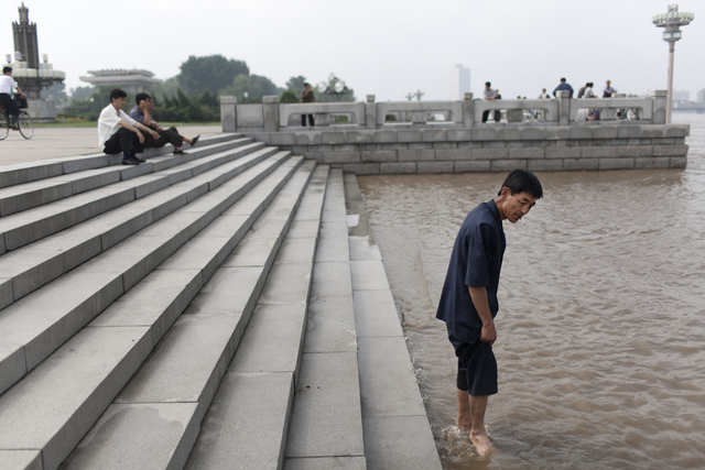 , 'A man wades into the Tae Dong river where banks are flooded high above the normal water level in Pyongyang, North Korea,' 2007, Museum of Contemporary Photography (MoCP)