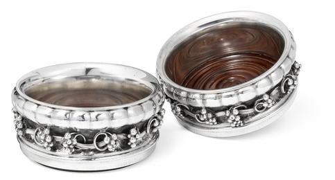 A pair of sterling silver bottle coasters with grapes. Carved mahogany bases.
