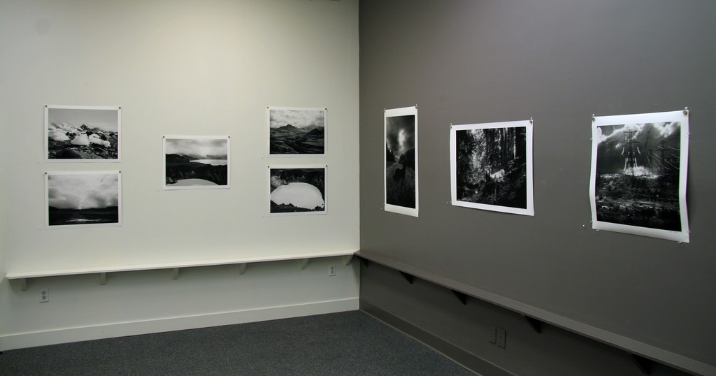 """White wall: Work by Dianne Kornberg,  """"The landscapes were photographed on a geology trip to Greenland (""""Kulusuk"""") and Iceland in 2002.  I used a medium format film camera, and printed on Hahnemuhle rag paper.""""; Grey wall: Work by Glenn Rudoplh"""