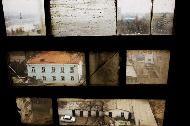", 'Khujand viewed through a window in the Leninabad Hotel. The city was established by Alexander the Great 2,500 years ago on the banks of the Syr Darya (framed in the upper left corner). From ""Two Rivers"",' 2009, Magnum Photos"