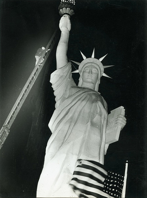 Weegee, 'Man climbs 85-foot ladder to secure torch on the plastic Statue of Liberty erected at Times Square for the Sixth War Loan Drive, New York', 1944, Elizabeth Houston Gallery