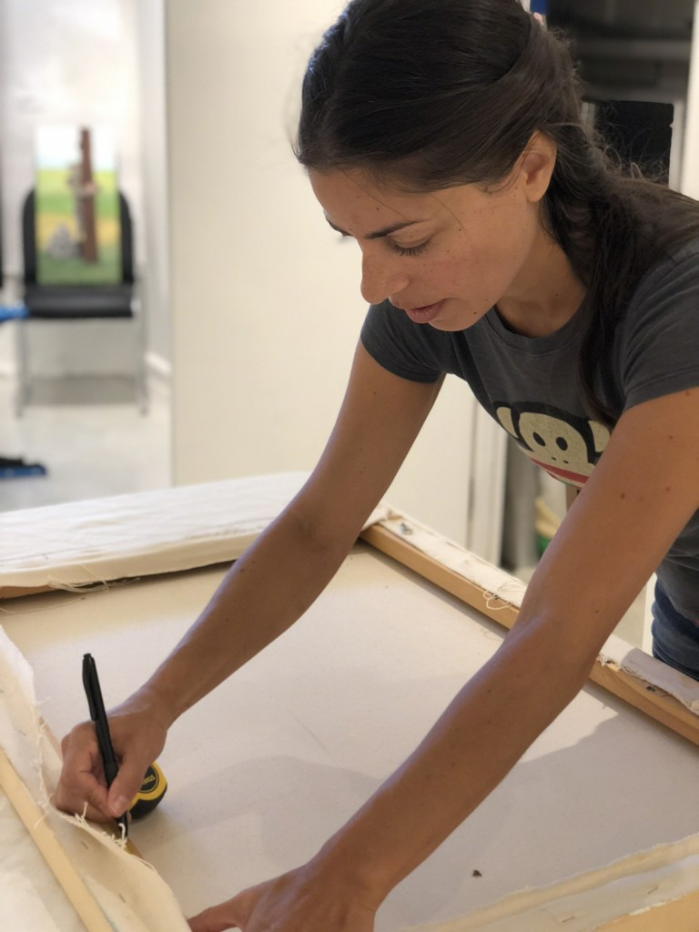 Artist Raquel Fornasaro wiring a painting for hanging