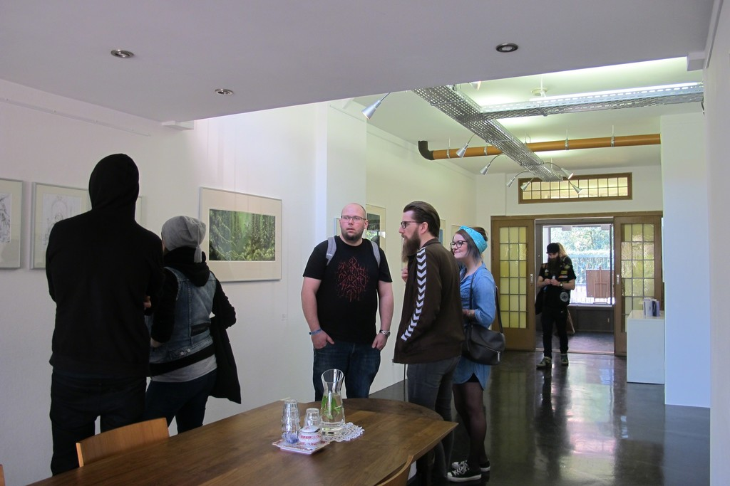 Installation overview with visitors during Roadburn Festival for the solo exhibition 'Brilliant Shadows' by Arik Roper.