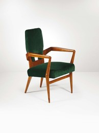 An armchair with a wooden structure and green fabric upholstery