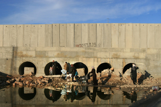 Alex Levac, 'Palestinian Families walk by the West Bank Separation Wall in Dahiyat al Barid, a Palestinian neighborhood in northern Jerusalem. In several locations, the Wall severs predominantly-Palestinian residential areas, leaving parts of it outside the wall, and parts of it in it. December, 2007', 2007, Ronald Feldman Gallery