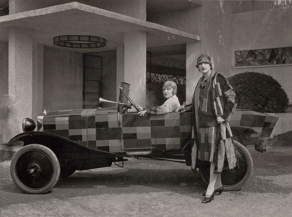 Two models wearing fur coats designed by Sonia Delaunay and manufactured by Heim, with the car belonging to the journalist Kaplan and painted after one of Sonia Delaunay's fabrics, in front of the Pavillon du Tourisme designed by Mallet-Stevens, International Exposition of Modern Industrial and Decorative Arts, Paris 1925. Bibliothèque nationale de France, Paris. Courtesy Tate Modern.