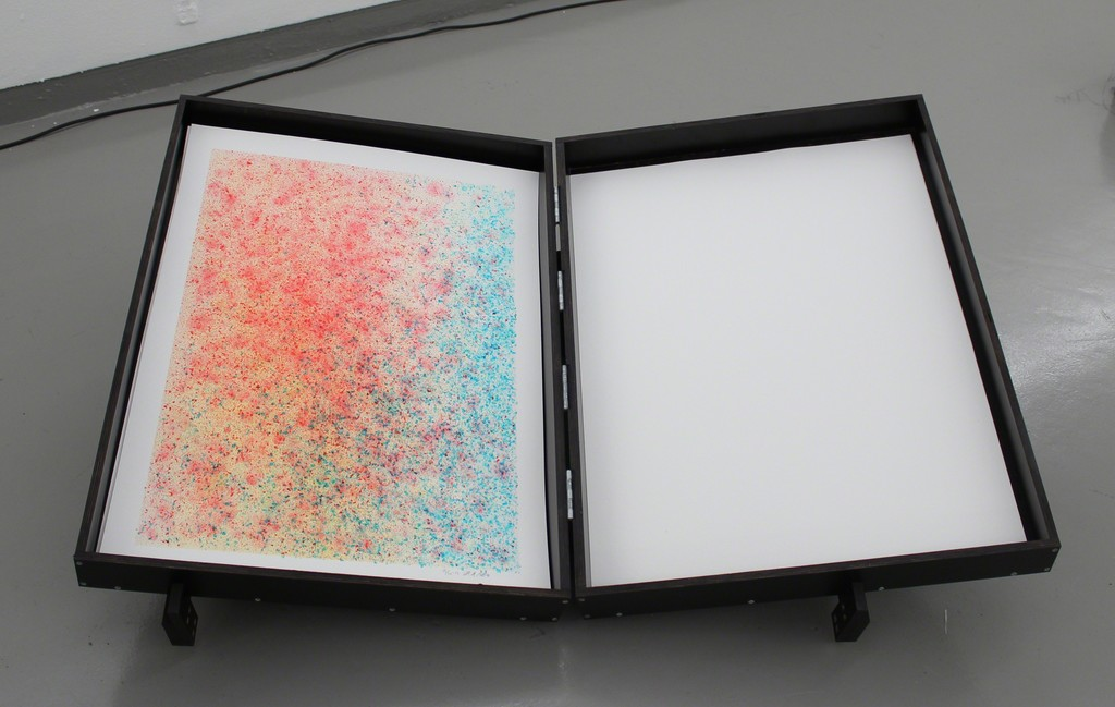 SB007 Watercolour Tool (Installation), 2016, Panels, electronics, paper and soap, 160 x 90 x 135 cm. With help from soap bubbles SB007 paints watercolors in red, yellow and blue. The colour of the soapwater is controlled by the daylight, and the colour is blown out in bubbles bursting on the paper consequently leaving a mark. Slowly the day appears on the paper. Aware of its own nature-romantic tradition the SB007 works with the 'special' Nordic light as a catalyst of the artistic process.
