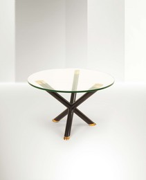 a table with lacquered wood stands and coppered metal details