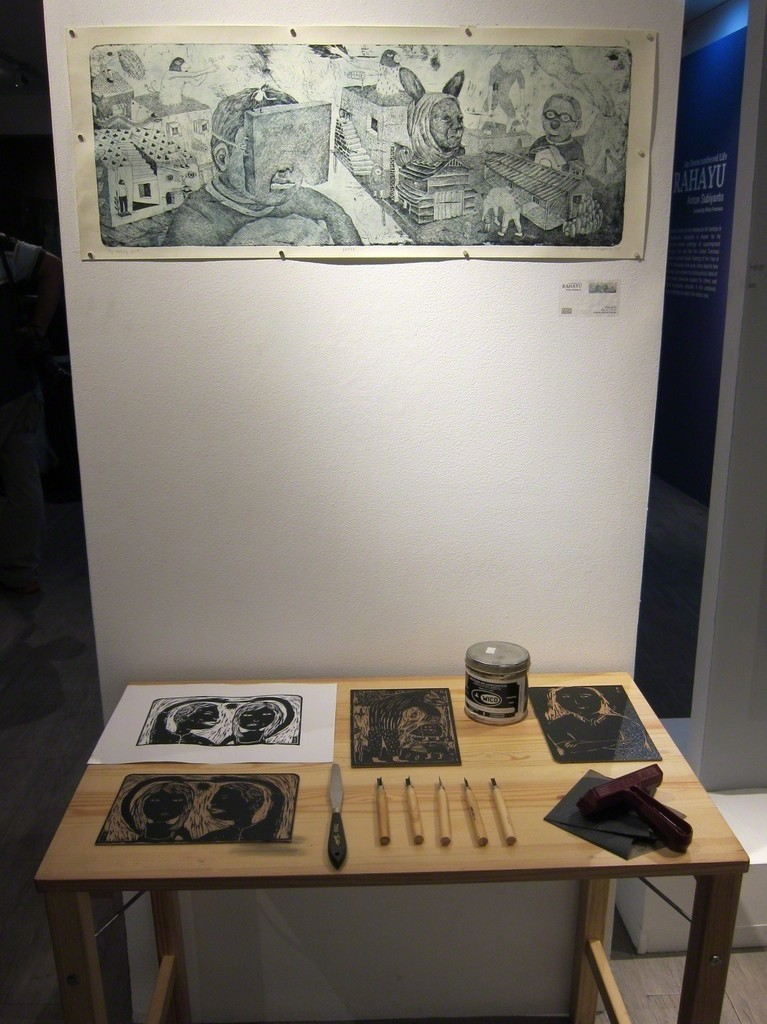 "The etching print, ""After""; beneath are the tools, materials, and finished product of the Wood Cut Print Demonstration held during the exhibit's opening."