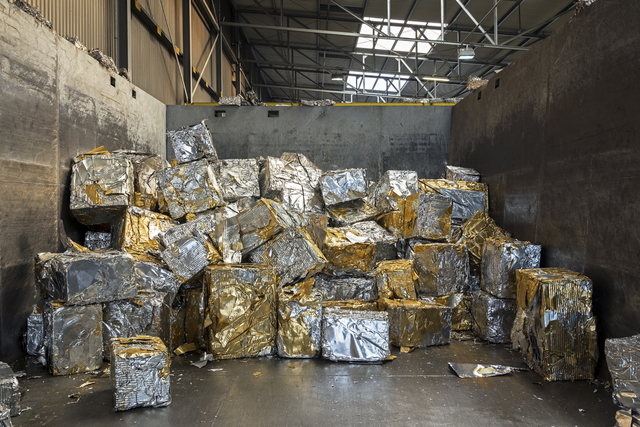 , 'Blocks of compressed aluminum scrap. Each block weighs approximately 200 kg and contains a small quantity of gold-colored lacquer typically used for beer can covers. In a specific recycling smelter, the lacquer is burnt and the molten aluminum is cast into new blocks that can be used to produce new cans, among other things.,' , Anastasia Photo