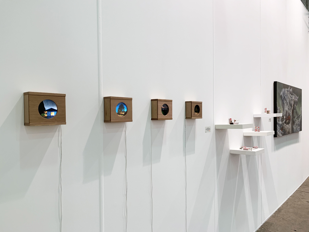 MAY SPACE at Booth G09 - Installation I, 10th September, 2019, featuring: Waratah Lahy, 'Welcome Home'; 'House hiding behind trees'; 'Twofold'; 'Park at night 2', 2019, oil on glass, recycled Tasmanian oak light boxes. Mylyn Nguyen, collection of matchbox sculptures. James Guppy, 'Fire and Ash,' 2019, acrylic on polycotton.