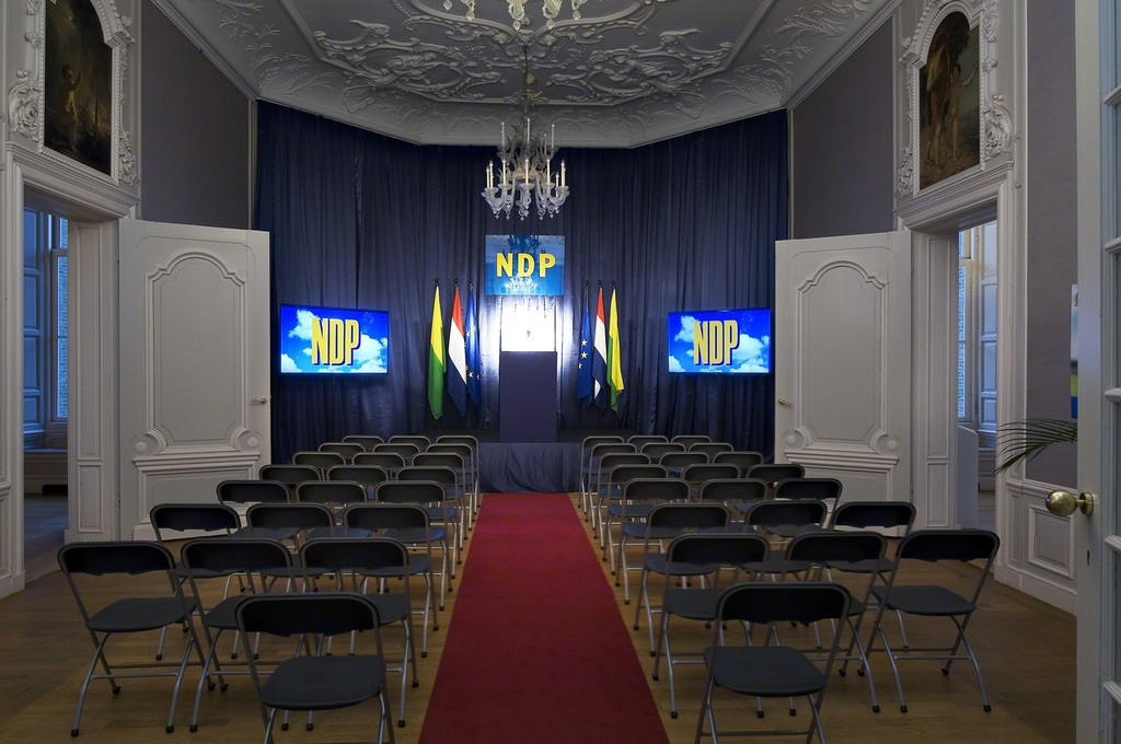 Guillaume Bijl. Nieuwe Demokratische Partij (A New Democratic Party). Installation with chairs, stage, flatscreens, flags, palms, lights, music, curtain, posters, pulpit etc, 2016. 500 x 800 x 1100 cm
