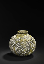 A round stoneware vase modelled with branches in relief.
