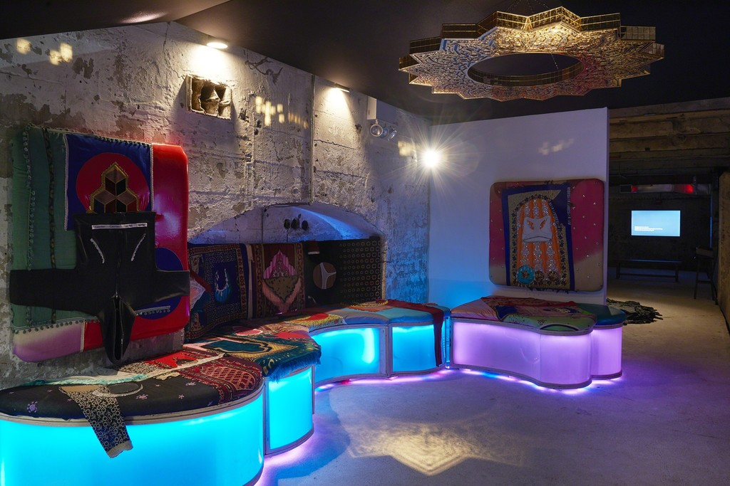 Baseera Khan, [Feat.], 2018, installation view, SculptureCenter, New York, 2018. Custom lounge with eight unique seating panels with pleather, artist's underwear, prayer rugs, and LED lighting, fourteen karaoke videos, acoustic fabric ceiling, black and gold mirrored plexiglass chandelier. Dimensions variable. Courtesy the artist and OSMOS, New York. Photo: Kyle Knodell