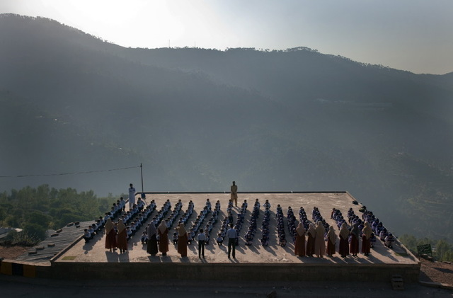 ", 'Just outside the hill town of Muree, in the foothills of the Himalayas and overlooking Islamabad and Rawalpindi, students line up on the roof of the Hira School, a privately run religious school with the motto, ""Education in Koran and Computer, side by side."" Pakistan,' 2009, Anastasia Photo"
