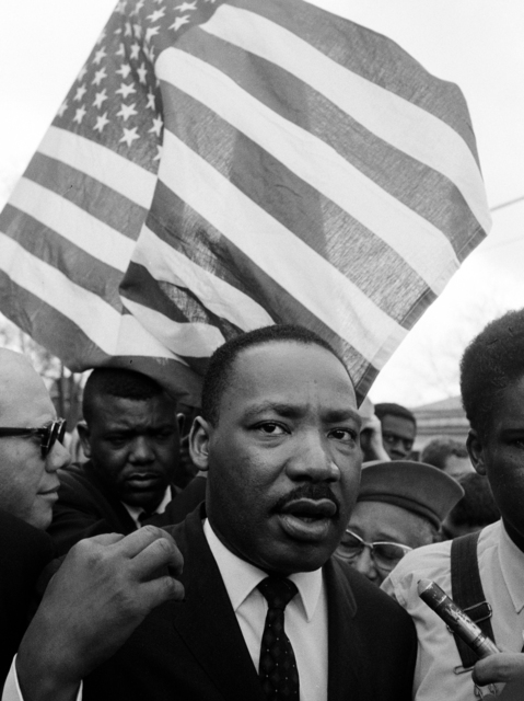 , 'Martin Luther Kinj jr. with Flag during Selma March,' 1965, CAMERA WORK