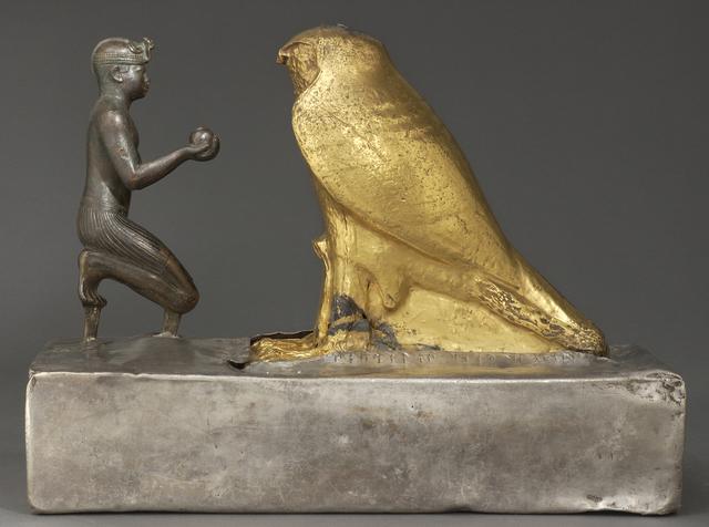 'Taharqa présente des vases à vin au dieu Hémen (Statuette of Taharqa and the Falcon God)', bronze (king), gold plated greywacke (Hemen) plated wooden base, silver, Musée du Louvre