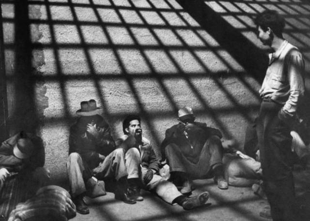 ", 'A group of illegal Mexican immigrants sprawled on floor of border patrol jail cell await deportation back to their homeland during ""Operation Wetback"", 1955,' , Monroe Gallery of Photography"
