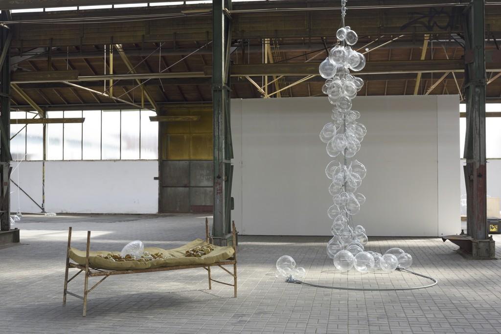 Koen Vanmechelen, Eggcord. 2008. Glass, steinless steel. Koen Vanmechelen, Instead of Sleeping. 2012. Glass, old bed. Courtesy: Fondazione Berengo. Photo credit: Peter Cox.