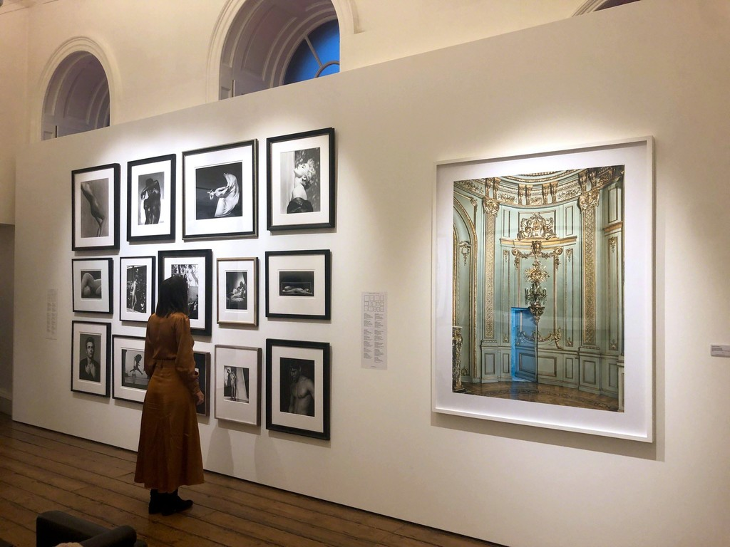 "Salon style wall including work by Barbara Morgan, Helmut Newton, Herb Ritts, Roy Schatt and Ruth Bernhard - Michael Eastman's ""Secret Doorway, Buenos Aires/2017"" featured at Photo London 2019"