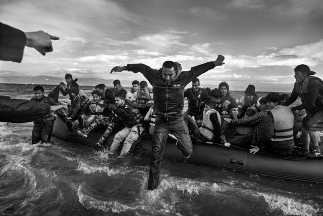 , 'Volunteers help refugees, primarily from Syria, Iraq and Afghanistan, disembark on the island of Lesbos, Greece, near Turkey.,' 2016, Monroe Gallery of Photography