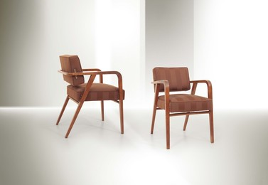 a pair of chairs with a wooden structure and fabric upholstery