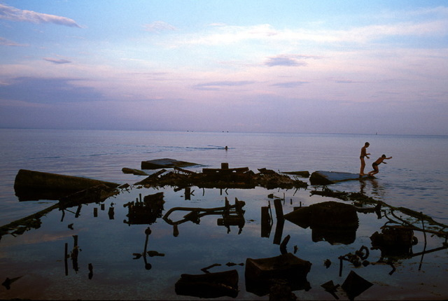 , 'A scene at dusk along the waterfront of Feodosia is dominated by the remains of the rusted out hull of a ship that local kids play on. Feodosia, Crimea,' 1993, Anastasia Photo