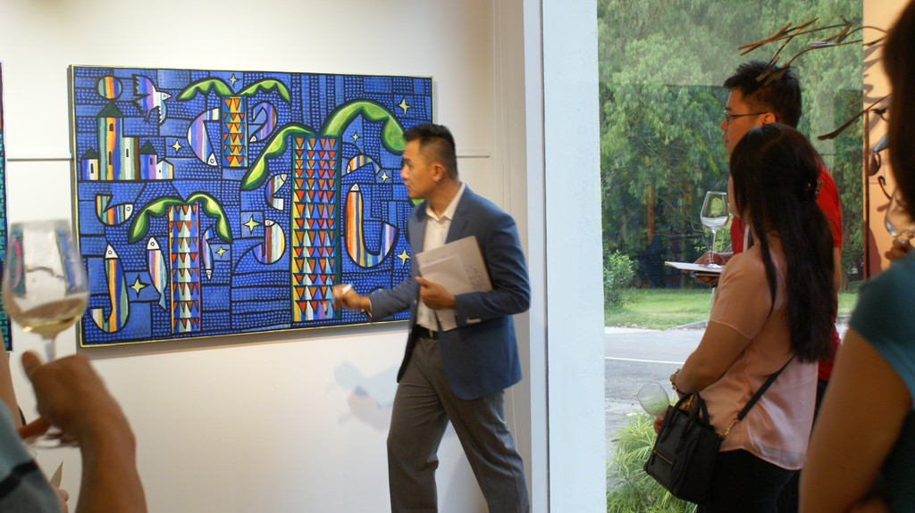 Gallery co-founder Weiren Loh, explains to guests on the significance of Rafael Romero's title work Territorio de Paz.