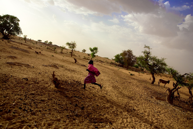 , 'A young girl runs through a displacement camp in Darfur.,' 2005, Anastasia Photo