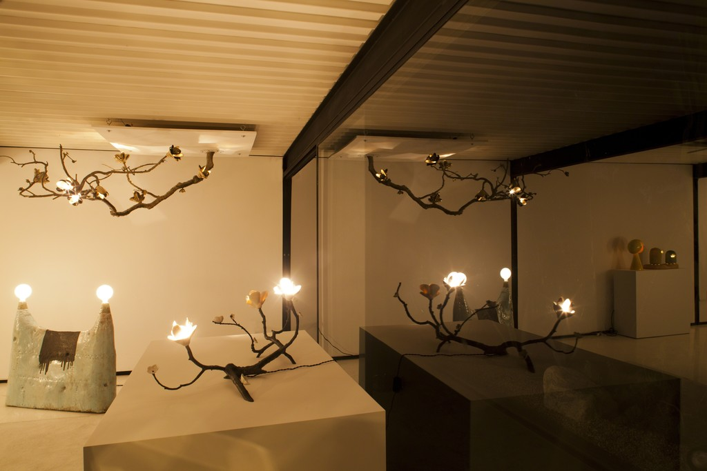 """David Wiseman Unique large ceiling mounted Branch illuminated sculpture in brushed bronze with polished bronze magnolia blossoms. 2012. 72""""(L) x 34""""(W) x 25""""(H)  David Wiseman Unique bronze table branch illuminated sculpture with porcelain blossoms. 2009. 43"""" (L) x 23"""" (W) x 16.5"""" (H)  Lee Hun Chung Sky blue double lamp Glazed Ceramic, incandescent light bulbs, 2010 100W x 15D x 90H cm 39.3W x 6D x 35.4H Inches"""