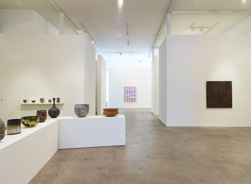 "Installation view of ""Transfigured."" with (left) ceramics by Jay Kvapil, (center) paintings by Sarah Mikenis;  (right) paintings by Lionel Sabatte´"