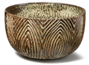 A circular stoneware bowl. Exterior modelled with fluted relief decor. Decorated with Sung glaze.