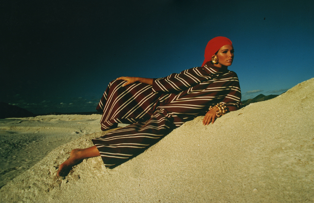 , 'Ann Turkel reclining on sand dune in brown-striped caftan & red scarf,' 1968, Deborah Bell Photographs