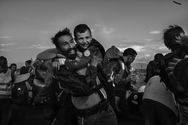 , 'A volunteer on Lesbos, Kadoni Kinan, 26, pulled a young Syrian boy from a raft that had just arrived from Turkey,' 2015, Monroe Gallery of Photography