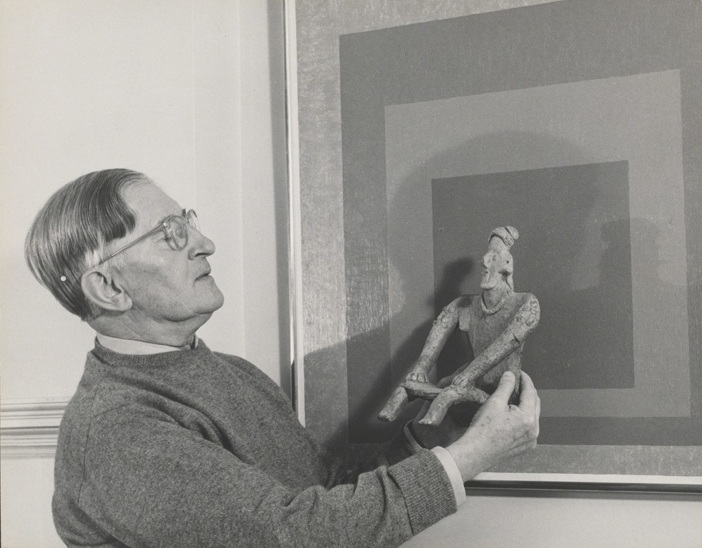 Lee Boltin, Untitled (Josef Albers Holding West Mexican Figure in front of Homage to the Square: Auriferous), 1958. Gelatin silver print. The Josef and Anni Albers Foundation, Bethany, Conn., 1976.28.923. © Lee Boltin. Photo courtesy the Josef and Anni Albers Foundation