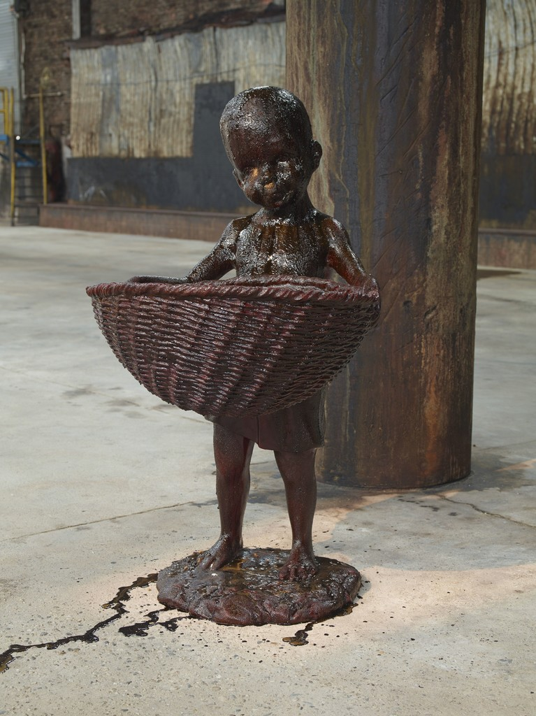 """African Boy Attendant Curio with Molasses and Brown Sugar, from """"The Marvelous Sugar Baby"""" Installation at the old Domino Sugar Factory Warehouse. (Front Basket)"""