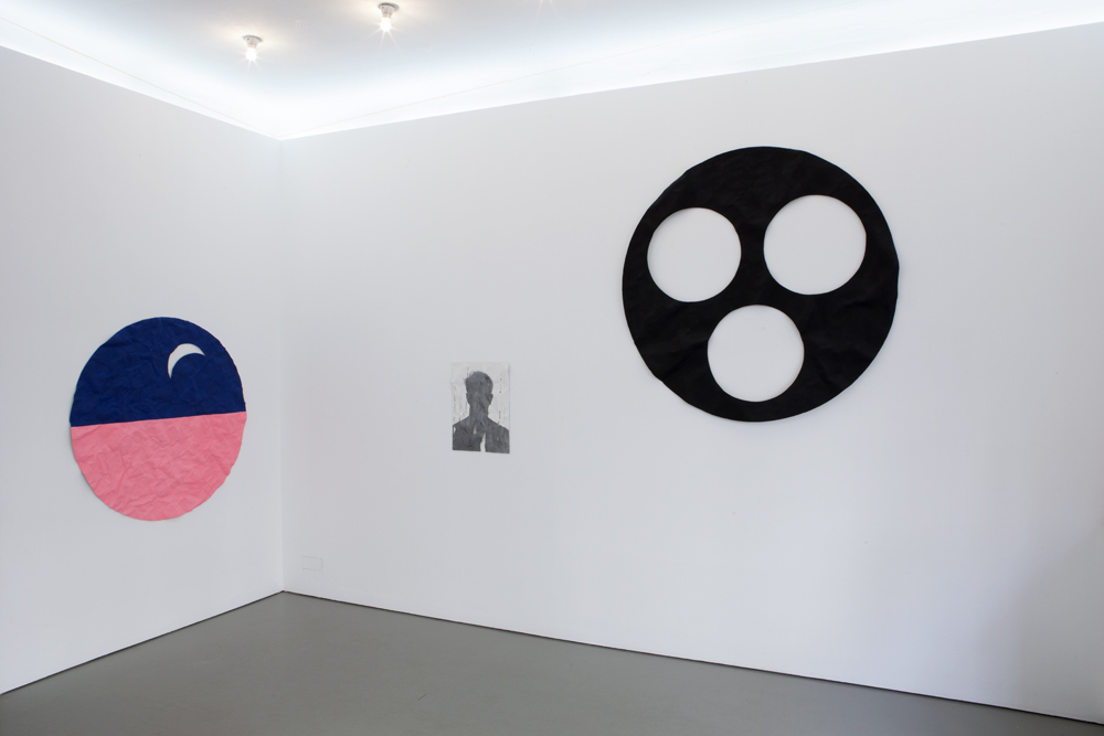 View of the exhibition 'DEAD FLAT' by Gil Shachar with three wall objects. The middle object is a portrait of a shadow of the artist himself in graphite on a epoxy cast of a wrinkled paper;  photo: Lukas Heibges