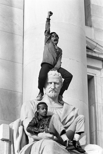 , 'Boy gives raised fist salute on a statue in front of the New Haven County Courthouse during a protest against the Bobby Seale and Ericka Huggins trial, New Haven, Connecticut,' 1970, Steven Kasher Gallery