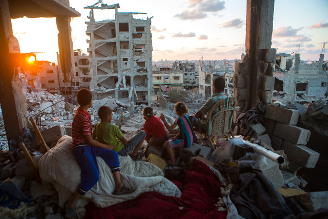 , 'Palestinian family members sit in their home, which was destroyed during Operation Protective Edge (Tsuk Eitan), in al-Tuffah district in Gaza City. Over 18,000 housing units were destroyed or damaged, and 2,000 Palestinians were killed during 50 days. September, 2014,' 2014, Ronald Feldman Gallery
